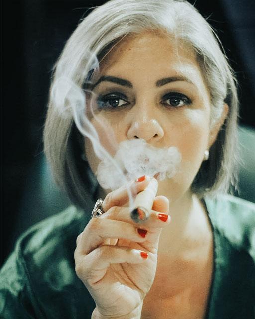 Cynthia Gonzalez (of Mujeres Entre Humos) in portrait, smoking a cigar