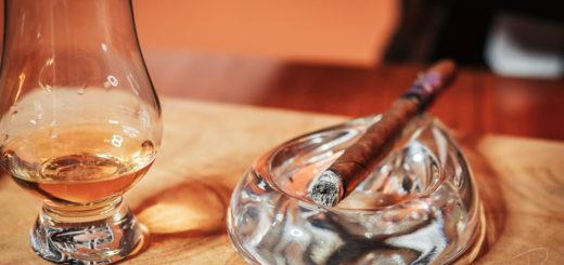 A freshly lit Hiram and Solomon Travelling Man Lancero cigar with a glass of Glenlivet Captains reserve